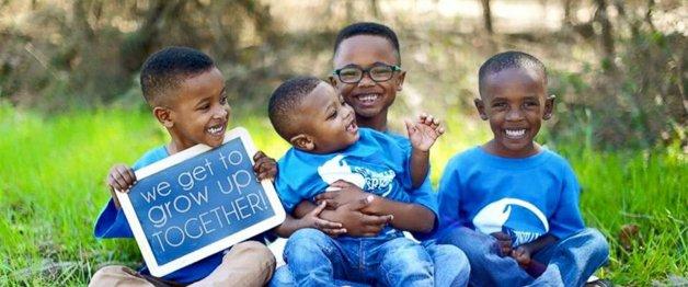 Os irmãos com um quadro que diz: «Nós vamos crescer juntos»